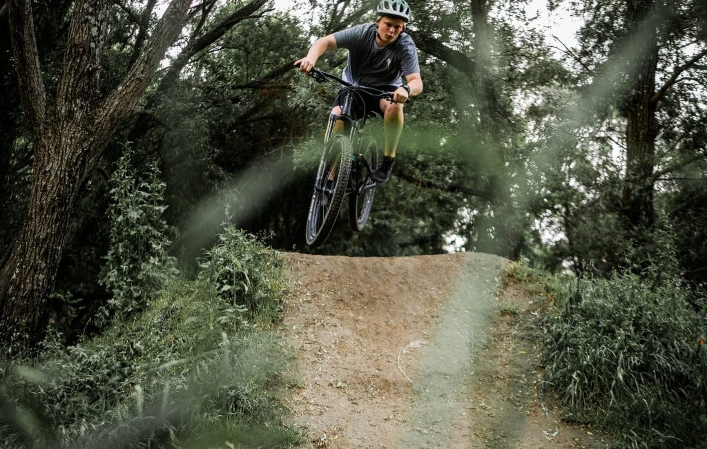 Jeune homme qui amorce un saut en vélo tout terrain