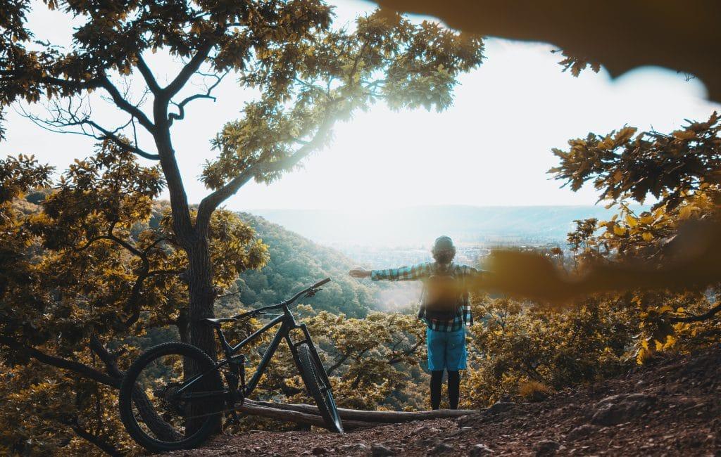 Vélo de randonnée posé sur un arbre avec son propriétaire face à la nature dans une foret