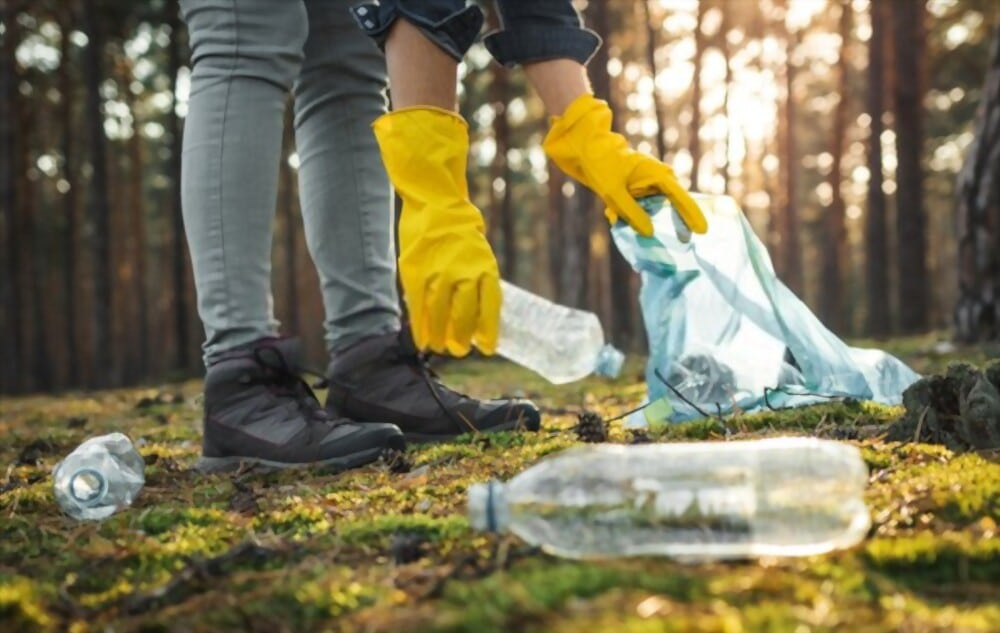 Homme ramassant des déchets plastiques (bouteilles, sacs) dans la nature.