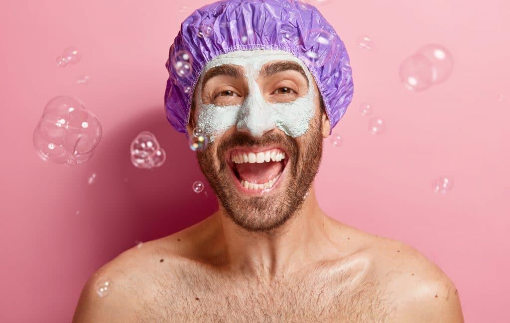 Homme heureux qui se fait un masque pour le visage pour prendre soin de sa peau